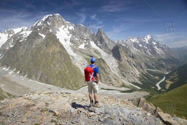 A male hiker is looking over the Val Veny, near Courmayeur, wit Mont Blanc dominating the sky line. This is halfway the Tour du Mont Blanc, a classic trekking around the highest peak of the Alps, that goes through France, Italy and Switzerland.