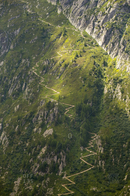 A steep mountain trail is winding up a slope above Chamonix in the French Alps. This is part of the Tour du Mont Blanc and also used by the runners of the Ultra Trail du Mont Blanc.