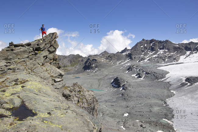 A hiker standing on a rocky peak near the Rosa Blanche. He is looking over a barren landscape, created when the glaciers retreated. This is halfway the Haute Route, a classic trekking in Europe.