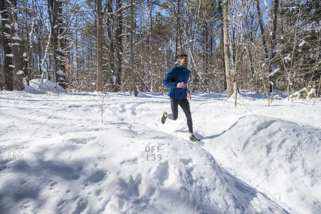 A male athlete running on a trail covered in snow on a bright sunny winter day.