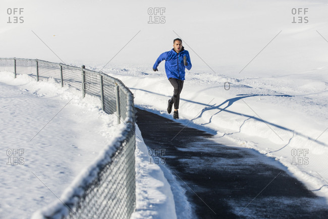 Running working out on a track in winter