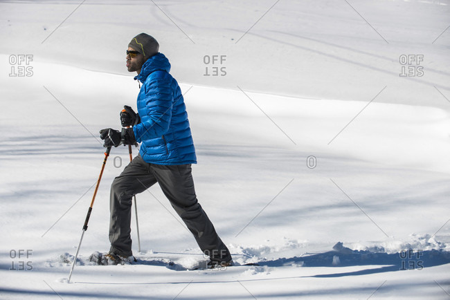 A man snowshoeing in a snow covered field on a sunny winter day.