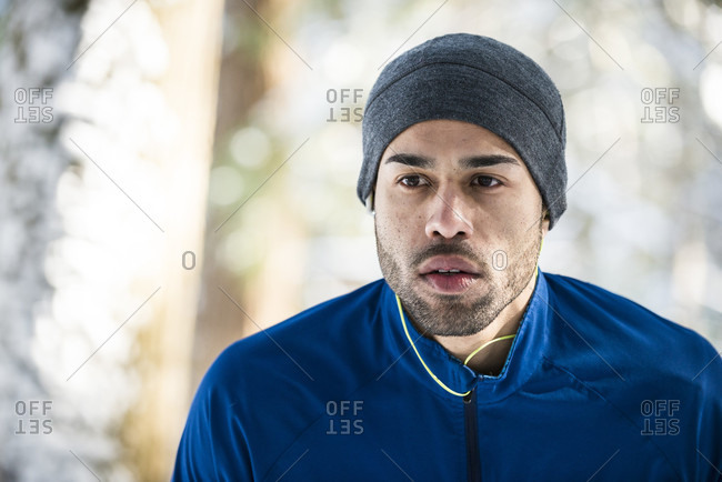 A male athlete running on a winter day listening to ear buds.