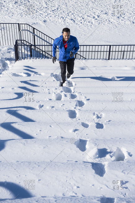 Athlete runs up snow covered stadium seats during a winter workout.