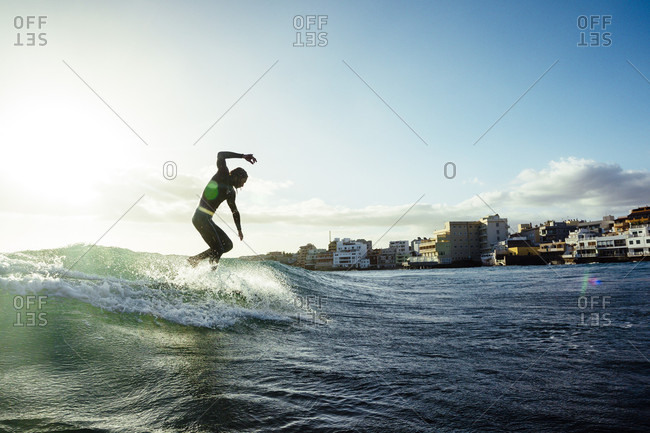 A man surfs a small wave on his longboard