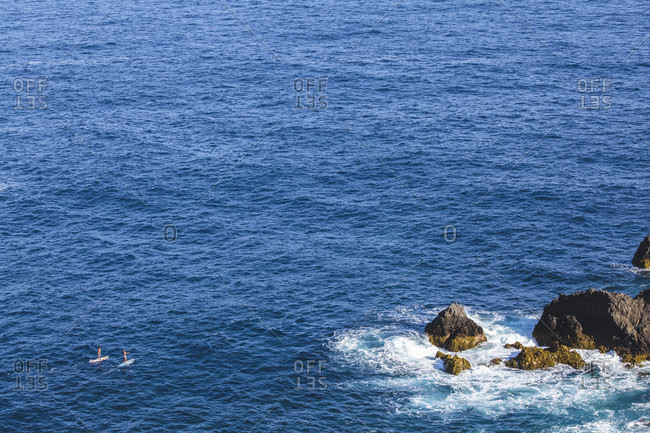 Distant view of couple paddling on their surfboards in beautiful sea, Tenerife, Canary Islands, Spain