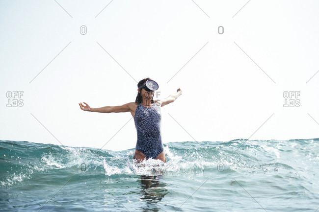 Woman in a swimsuit and diving goggles walking out of water off beach, Tenerife, Canary Islands, Spain