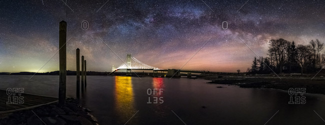 Deer Isle Bridge Milky Way Panorama Maine  The Milky Way arcs over the Deer Isle Bridge on a cold night in February.  The bridge is lit up from the headlamps of trucks.  Nikon D810A, Nikon 14-24mm f/2.8 lens @ 14mm, f/2.8.  10 vertical shots at ISO 10,000 for 20 seconds each, 30 degrees of panning between each shot, stitched in Photoshop.  I used the Nodal Ninja RD16-II rotator to make the panning easy and not need a headlamp to check the angle of rotation.