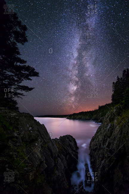 The Milky Way from the dramatic cliffs in Cutler, Maine, with the red glow of the tall antenna tower array at Cutler Naval Base in the background.
