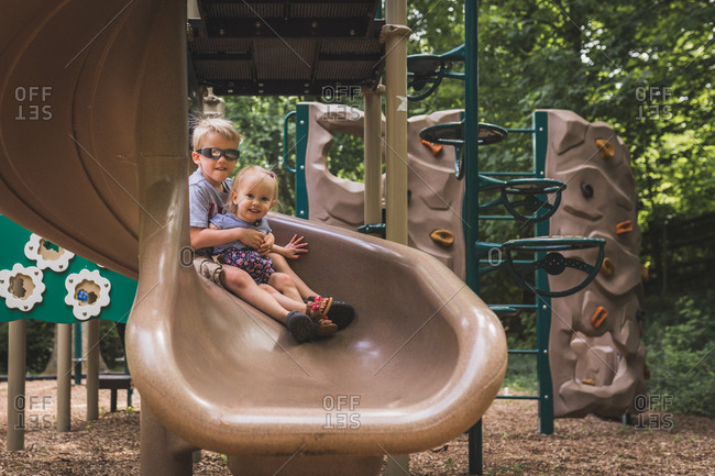 Siblings sliding down slide