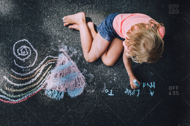 Girl drawing with sidewalk chalk