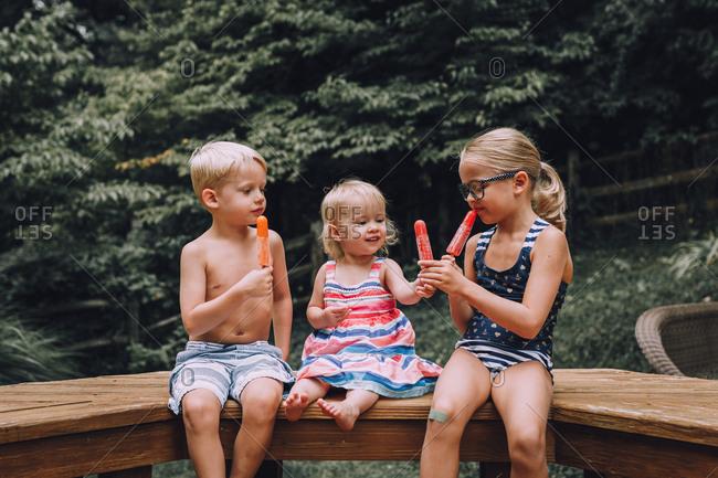 Kids eating popsicles outside