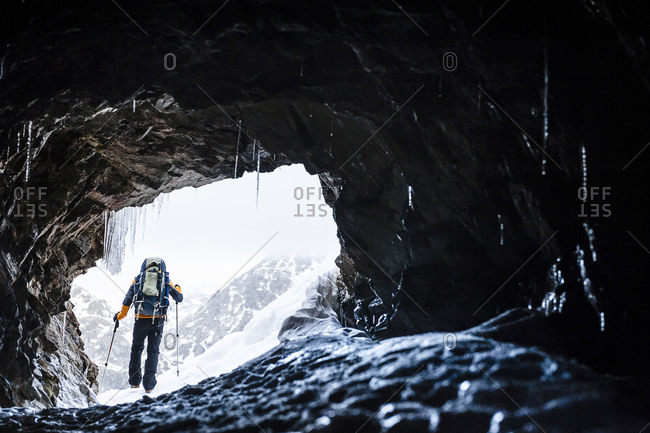 Silhouette of an alpinist  in the cave of a mountain in the middle of the snow in Vall del Fosca, Pirineos, Spain