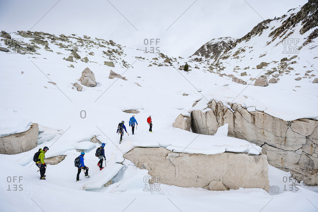 Group of alpinists crossing the snow in a row in Vall de Fosca, Spain