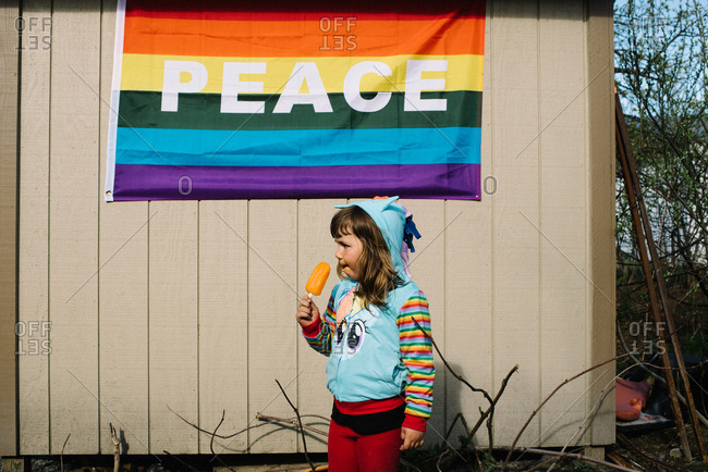 Little girl holding an ice pop standing below a rainbow peace flag