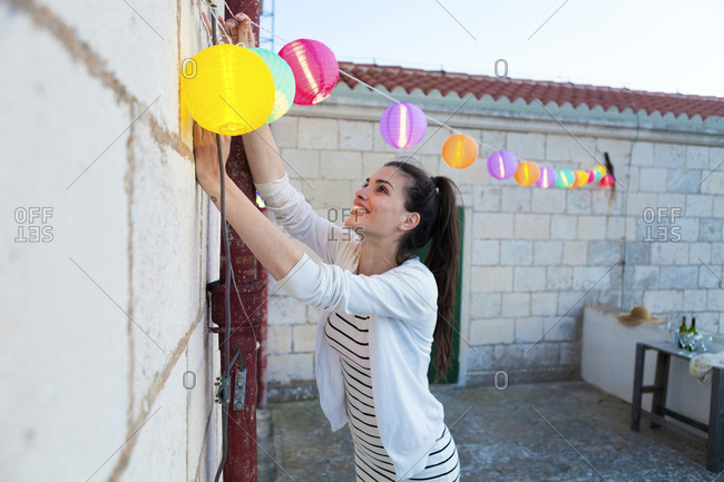 Young woman hanging  illuminated balloons on wall