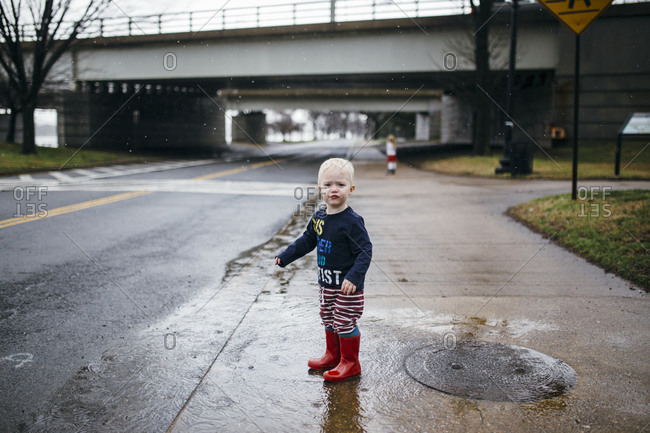 Toddler wearing galoshes standing in a puddle on a rainy day