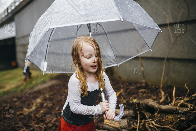 Girl with wet hair holding an umbrella on a rainy day