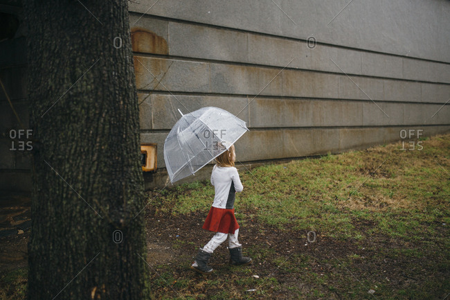 Young girl holding an umbrella walking outside on a rainy day