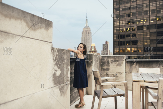 Girl standing on rooftop amid views of tall buildings in New York City