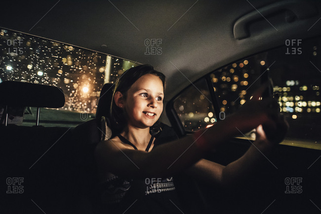 Girl taking a selfie in a car at night