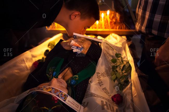 Vadeni, Moldova - August 15, 2015: Boy kissing body at funeral