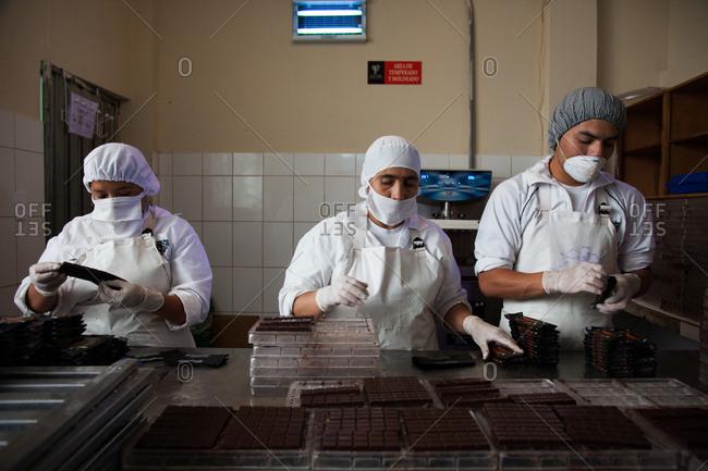 Ecuador - January 6, 2013: People making chocolate bars