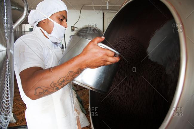 Ecuador - January 6, 2013: Man filling chocolate mixer