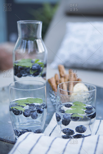 Water served in glasses with blueberries and mint