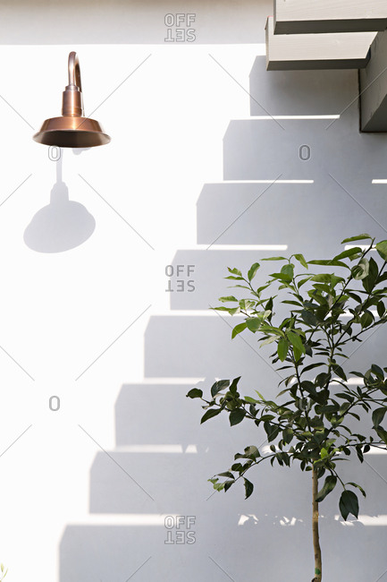 Shadow of stairs on white building with tree and copper light fixture