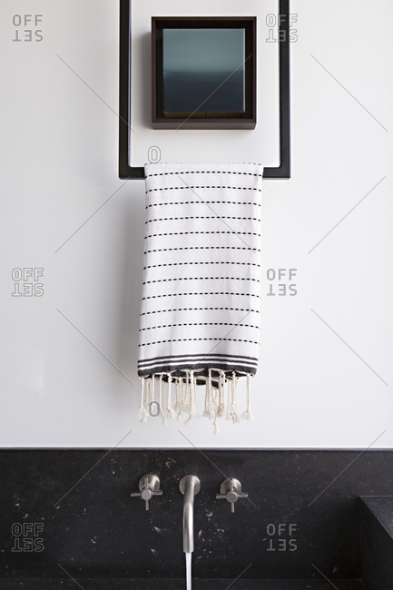 Hand towel hanging above bathroom sink