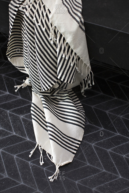 Bath towel hanging in a bathroom and touching floor