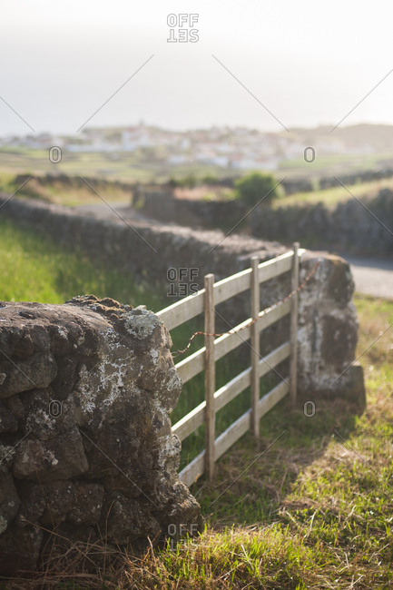 Wooden gate in a stone wall surrounding a pasture