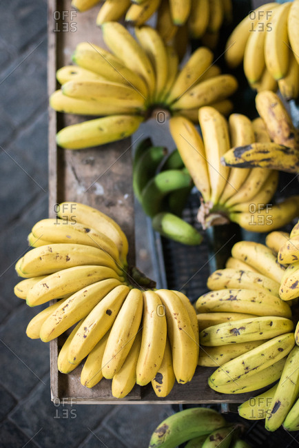 Bunches of ripe yellow bananas on a wooden display