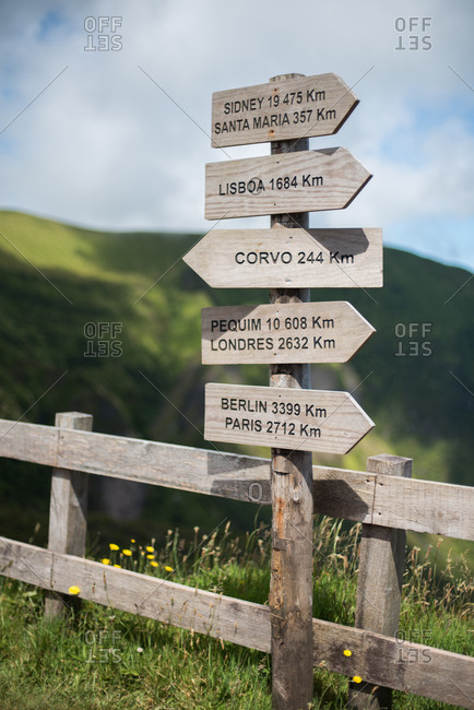Wooden Portuguese road sign pointing to different global cities