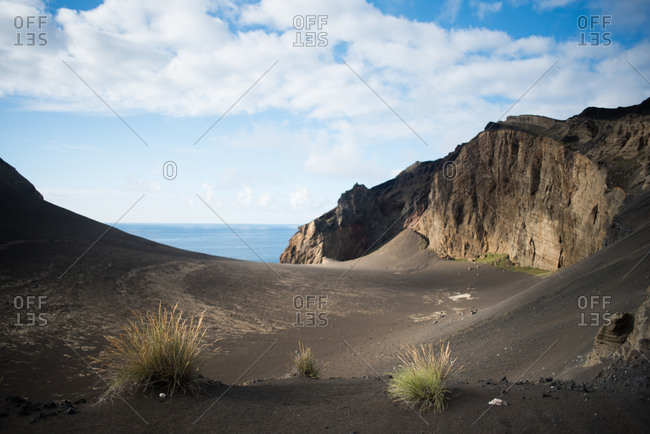 Sloping black sand hill between stone cliffs overlooking the ocean