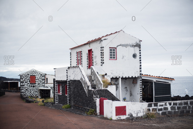 Traditional house beside the ocean with black stones and white mortar in Lajido, Portugal