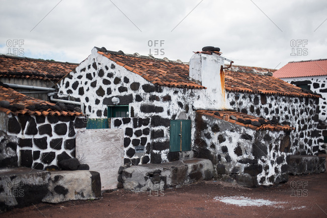 Traditional house with black stones and white mortar in Lajido, Portugal
