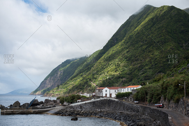 Roads running through a seaside village beneath green mountains on Sao Jorge Island, Portugal