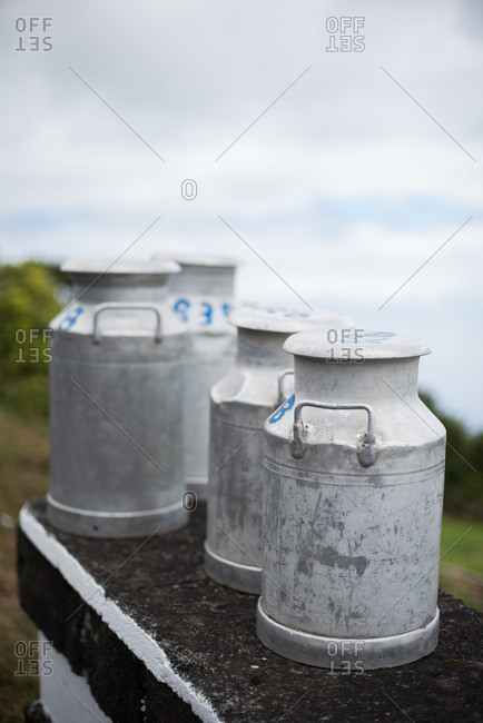 Milk canisters in a row on a stone wall outdoors