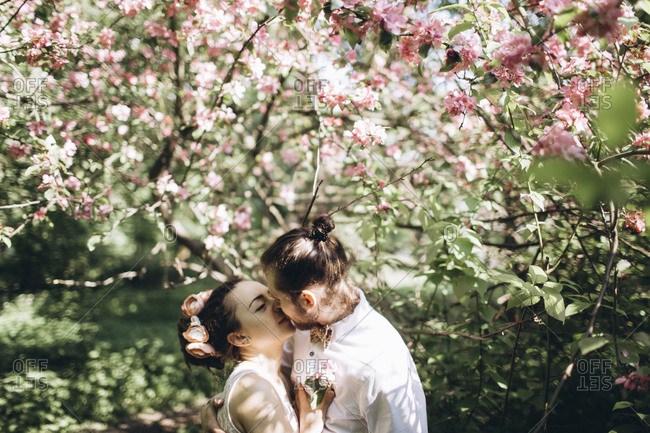 Middle Eastern couple kissing under flowering tree