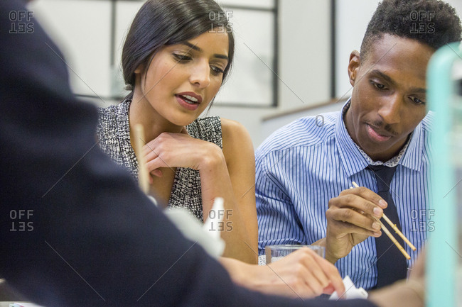 People eating with chopsticks in meeting