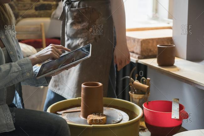 Caucasian women using digital tablet near pottery wheel