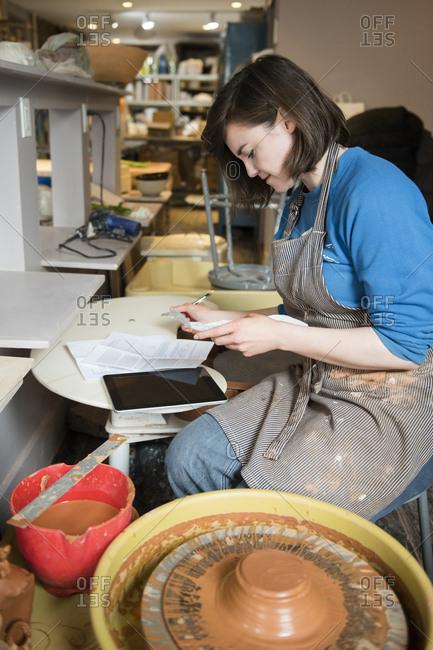 Caucasian woman reading paperwork near pottery wheel
