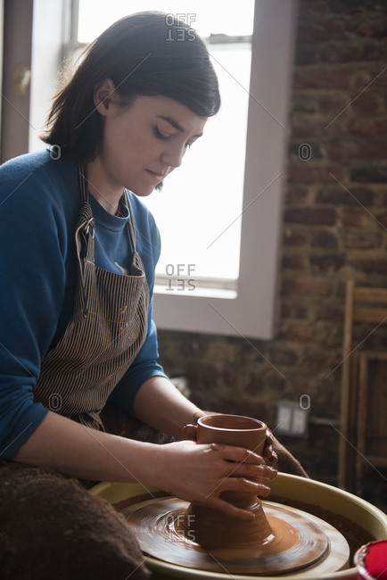Caucasian woman shaping clay on pottery wheel