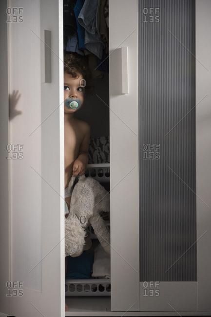 Caucasian boy hiding in closet peeking from doorway
