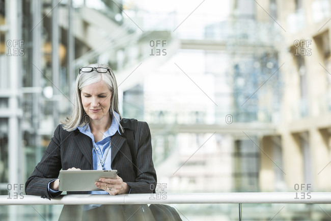 Caucasian businesswoman leaning on railing in lobby using digital tablet