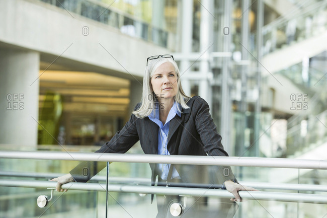 Portrait of serious Caucasian businesswoman leaning on railing in lobby