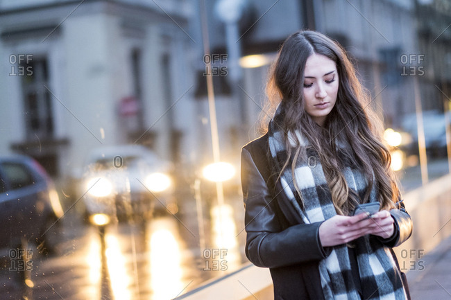 Serious Caucasian woman texting on cell phone outdoors