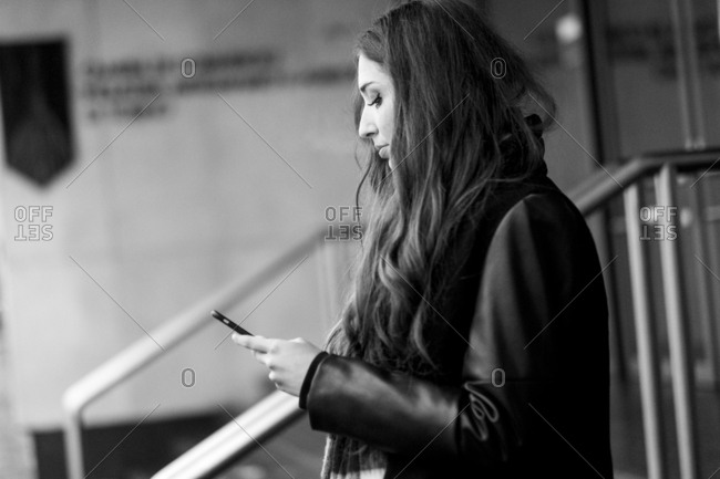 Serious Caucasian woman texting on cell phone
